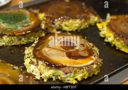Okonomiyaki cooking on a hot plate. - Stock Photo