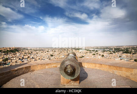 Old Cannon at tower of Jaisalmer fort and sandstone desert city view in Rajasthan, India - Stock Photo