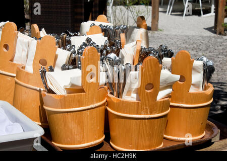 forks, spoons and knives prepared to be served in an outdoor cafe - Stock Photo