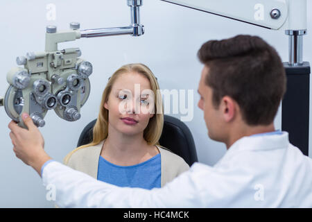 Optometrist interacting with female patient - Stock Photo