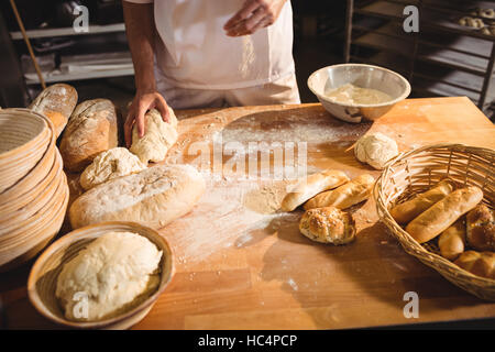 Mid-section of baker ready to knead a dough - Stock Photo