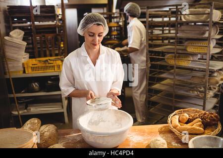Female baker sifting flour through a sieve - Stock Photo