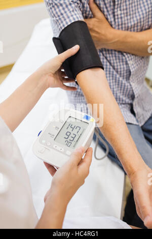 Female doctor checking blood pressure of patient - Stock Photo