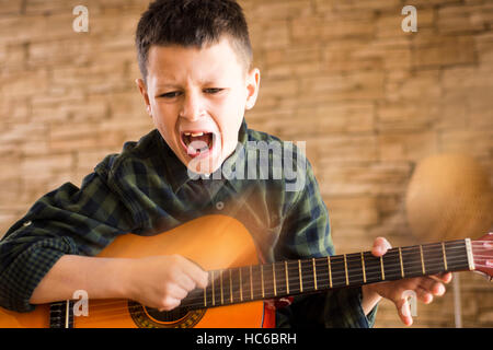 Young Boy Singing Out Loud While Playing Acoustic Guitar in Living Room - Stock Photo