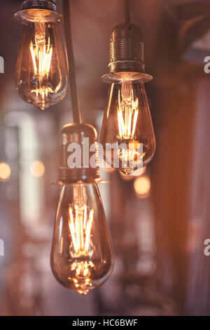Old Style Glowing Light Bulbs Hanging in Bar - Stock Photo