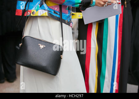 Woman with black leather Prada bag and colorful patterns before Max Mara fashion show, Milan Fashion Week street - Stock Photo