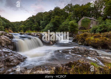 An old water mill sits on the other side of the river Teifi at Cenarth Falls - Stock Photo