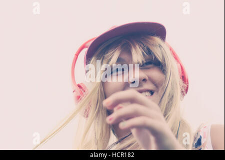 Girl listening to music on headphones - Stock Photo