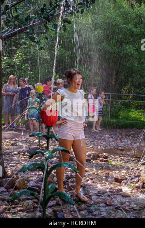 happy young woman gets wet by Fontaine in the Grand Peterhof Palace and The Grand Cascade and Samson Fountain in - Stock Photo