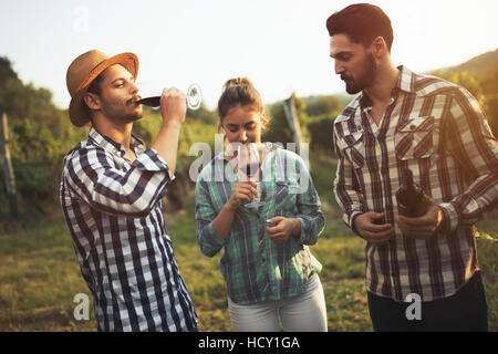 Happy wine tourists tasting wine in vineyard - Stock Photo