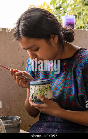 A young Mayan woman, wearing typical traditional dress, paints designs on pottery in a workshop in San Antonio Palopó, - Stock Photo