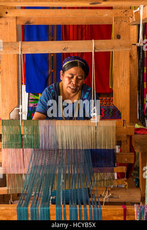 A  Mayan woman, wearing typical traditional dress,  weaves fabric on a foot-operated loom in workshop in San Antonio - Stock Photo