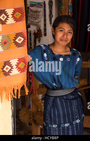 An attractive young Mayan woman wearing typical dress looks out the door of a weaving shop in San Antonio Palopó, - Stock Photo