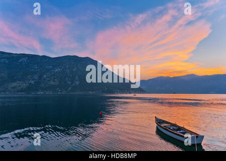 The boat in the sea at sunset with mountains in the background. The Bay of Kotor. Montenegro. - Stock Photo