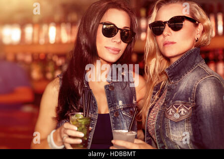 Two gorgeous women with refreshing drinks having fun in the outdoor bar, wearing stylish sunglasses and enjoying - Stock Photo