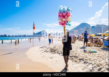 RIO DE JANEIRO - FEBRUARY 27, 2016: Brazilian beach vendor selling cotton candy floss approaches customers on Copacabana. - Stock Photo