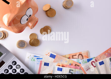 Concept savings and accounting with piggy bank and stacked coins and bills, and calculator on table and white background. - Stock Photo