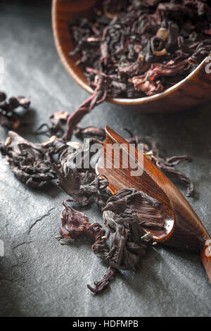 Hibiscus tea in the wooden bowl on the dark stone table vertical - Stock Photo