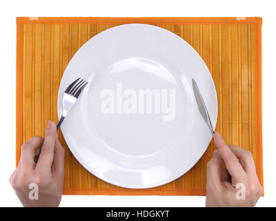 Hands hold fork and knife above plate on bamboo mat. All around Isolated. - Stock Photo