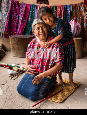 A young Guatemalan Mayan girl in traditional dress, about age 8 years, with her old grandmother.  The older woman - Stock Photo
