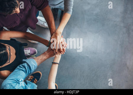 Top view image of group of young people putting their hands together. Friends with stack of hands showing unity. - Stock Photo