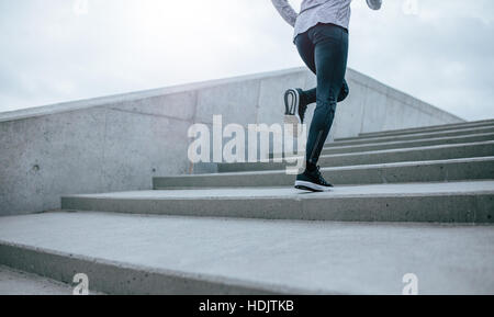 Low section shot of woman running up the stairs. Female legs climbing the steps in morning. - Stock Photo