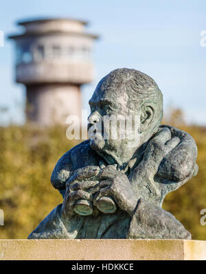 Bronze sculpture of Sir Peter Scott birdwatching with viewing tower at Slimbridge Wildlife and Wetlands Centre Gloucestershire - Stock Photo