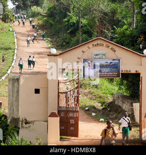 Students on their way through the gate of St. Charles Parish Church in Freetown, Sierra Leone - Stock Photo