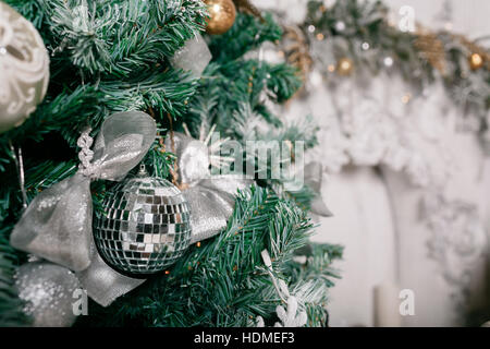 decorative disco ball close-up. Decorated Christmas tree on blurred, sparkling fairy background - Stock Photo