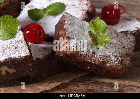 Delicious chocolate brownie cake with nuts closeup on paper. horizontal - Stock Photo