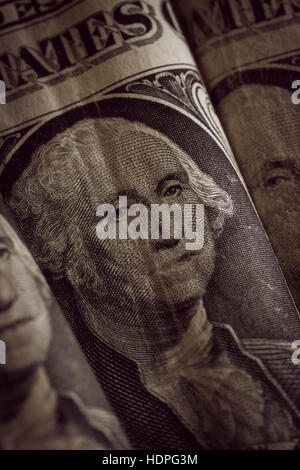 Old and crumpled United States one dollar bank notes photographed with shallow focus and an antique filter applied - Stock Photo