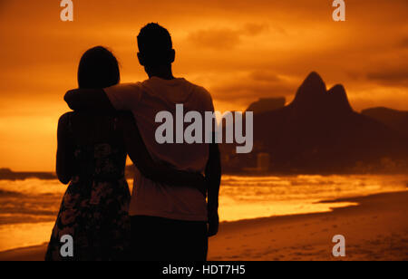 Love couple in arms outdoor on beach at sunset at Rio de Janeiro - Stock Photo