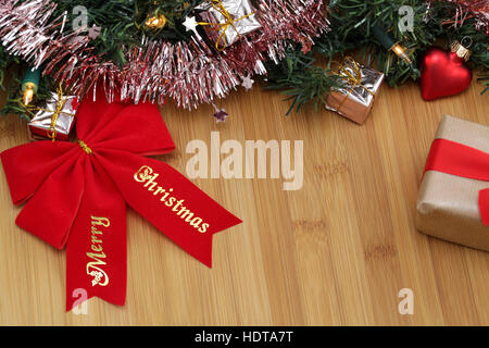 A red bow with the word Merry Christmas and Christmas decorations on a wooden board - Stock Photo