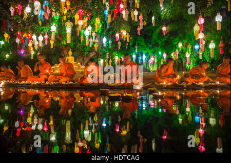CHIANG MAI, THAILAND - NOVEMBER 06, 2014: Young Buddhist monks sit meditating at a festival of lights loi krathong - Stock Photo