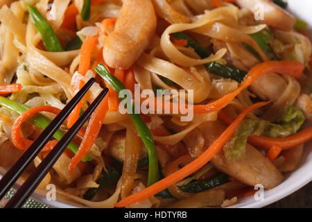 Delicious food: fried noodles with chicken and vegetables macro. horizontal - Stock Photo