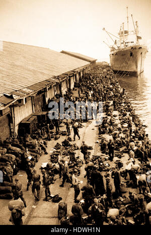 U.S. troops are pictured on pier after debarking from ship, somewhere in Korea. - Stock Photo