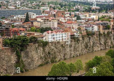 Georgia, Tbilisi. View from the fortress Narikala on Avlabari district , houses on a cliff , leaving the water in - Stock Photo