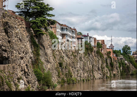 Georgia, Tbilisi. View on Avlabari district , houses on a cliff , leaving the water in the Kura River . - Stock Photo