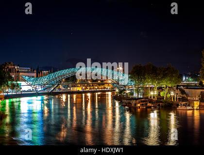 Georgia, Tbilisi night . View from the square Gorgasali at the Kura, Peace Bridge , Anchiskhati Basilica . - Stock Photo