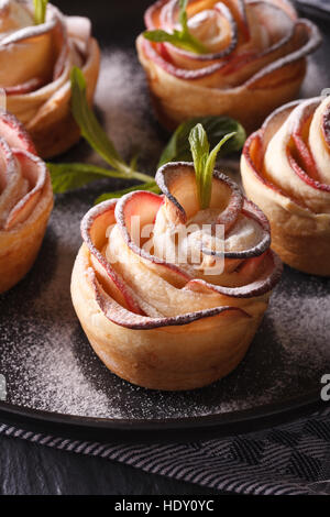healthy food: apple pie in the form of roses on a black plate macro. vertical - Stock Photo