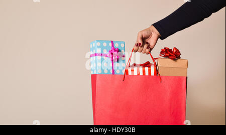 closeup of a young caucasian woman with her fingernails painted red holding a red shopping bag full of gifts wrapped - Stock Photo