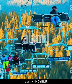 Skiers and snowboarders on a ski lift in Bukovel. Bukovel is the most popular ski resort in Ukraine. - Stock Photo