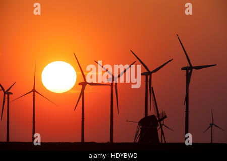 Wind turbines at the Eemshaven at sunset, Groningen, Netherlands - Stock Photo