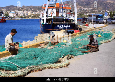 Fishermen repairing their nets in the harbour at agios nikolaos on the Greek island of Crete - Stock Photo
