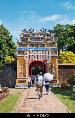 People walking into the entrance gate to the Hung To Mieu Temple. Imperial City (The Citadel), Hue, Vietnam. - Stock Photo
