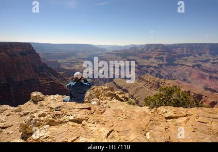 Adventure travel man at edge of the Grand Canyon south rim Pipe Creek Vista taking photo, Arizona USA rear view - Stock Photo
