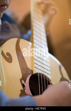 Boy playing a guitar decorated with a monkey - Stock Photo