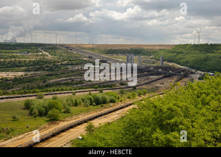 Parts of Garzweiler surface mine, shot from Jackerath viewpoint, with power plants and wind turbines behind. - Stock Photo