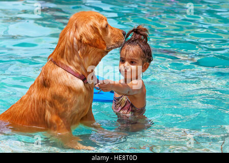 Funny photo of little baby swimming in outdoor pool, playing with retriever puppy. Children water sports activity. - Stock Photo