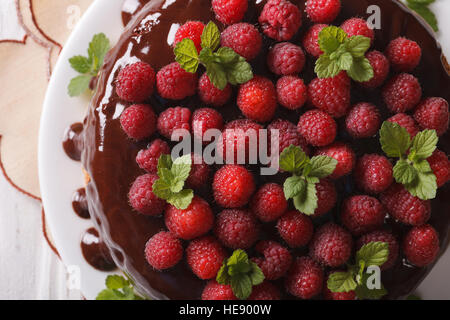 Chocolate raspberry cake with fresh berries close up on a white plate. horizontal view from above - Stock Photo